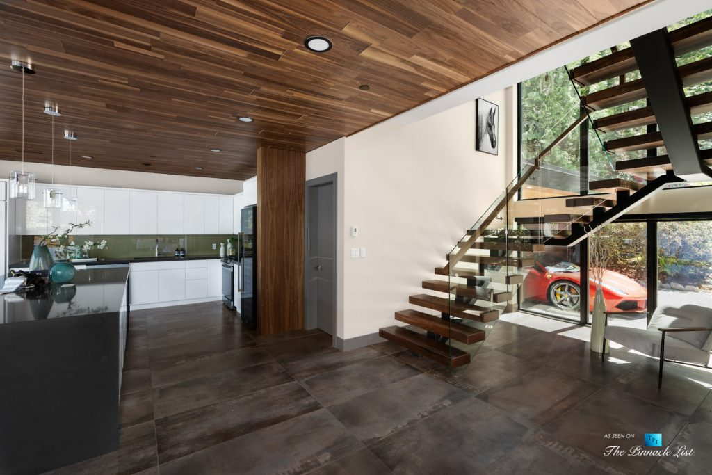 3350 Watson Rd, Belcarra, BC, Canada - Vancouver Luxury Real Estate - Kitchen and Glass Stairwell with Red Ferrari in Driveway
